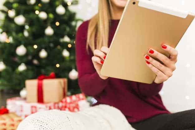 Femme avec une tablette devant son sapin de Noël